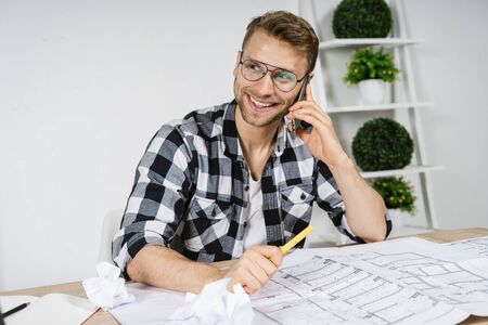 Happy young adult architect talking on smartphone and and discuss with client new house project. Businessman working in modern studio with blueprints, sitting behind table against copy space wall