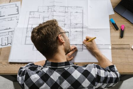 High angle top view of young adult project manager and architect working in professional bureau with blueprints, drawing or sketch of house project at office