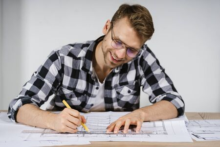 Happy and glad young adult architect working with blueprints in workspace office, making new renovation project for house with modern design interior