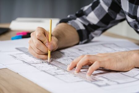 Cropped view of young adult architect and businessman working in modern studio with blueprints, making new housing project on sketch on building construction