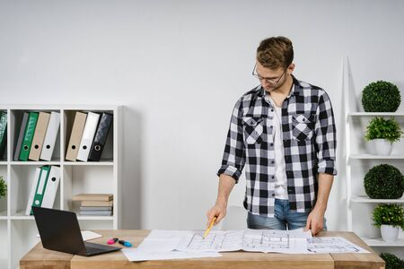 Confident young adult architect and freelancer working with blueprints in workspace office, pointing at documents, standing behind table against wall with copy space