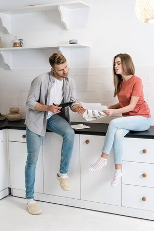 Minded and upset young adult woman and man spending morning in kitchen, reading important notification from bank while managing domestic finances and calculating their expenses 写真素材