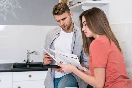 Thoughtful young adult woman and man standing in modern kitchen, reading important notification from bank while managing domestic finances, calculating their expenses, looking focused