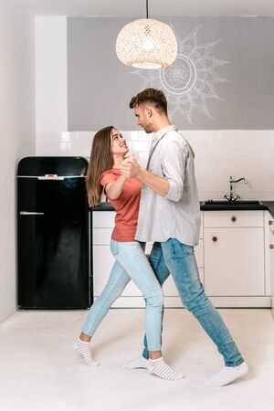 Side view of happy young adult man and woman dancing on kitchen, looking to each other, smiling, having fun and spending weekend together
