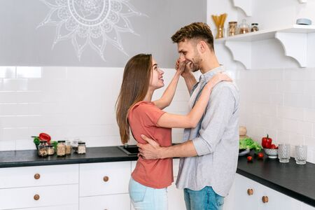 Side view of happy young adult husband and wife making rejoiced faces, smiling wide, dancing on kitchen together, spending weekend at home with modern interior