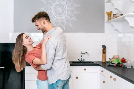 Side view of cheerful and happy young adult man dancing on kitchen together with woman, hugging her, laughing and having fun against wall with copy space 写真素材