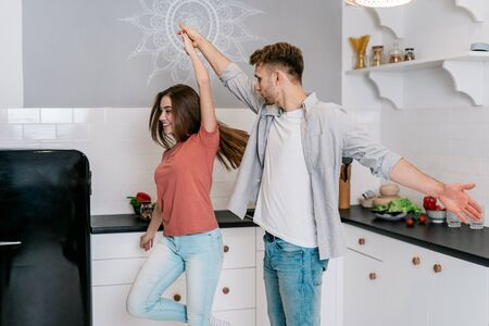 Happy young adult boyfriend and girlfriend dancing on kitchen together, moving, listening music, laughing at morning, spending weekend in house with modern interior