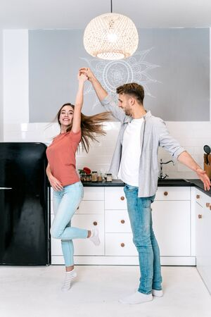 Joyful and happy young adult husband dancing on kitchen with wife, spending weekend at home together, having fun and smiling wide
