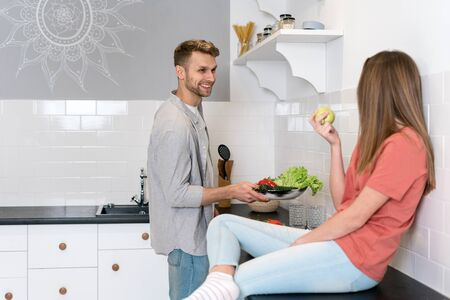 Happy young adult woman with man spending morning in kitchen, cooking healthy food together, smiling wide and having fun, standing against copy space wall