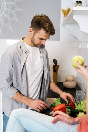 Concentrated young adult husband standing in modern kitchen together with wife, cooking healthy food, choosing fresh raw ingredients for meal