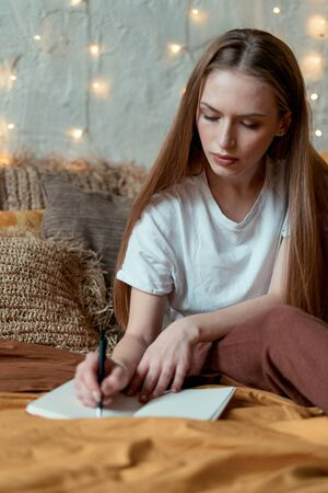 Dreamy and calm young adult woman write in notepad, resting in bedroom, spending morning at home, sitting on bed