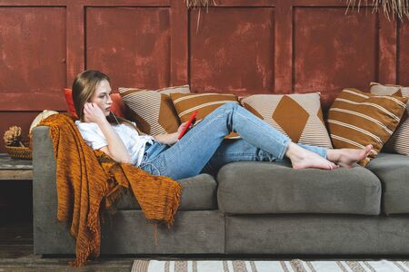 Side view of young adult woman using earphones on modern smartphone, listening music and spending free time at home, lying on couch in living room