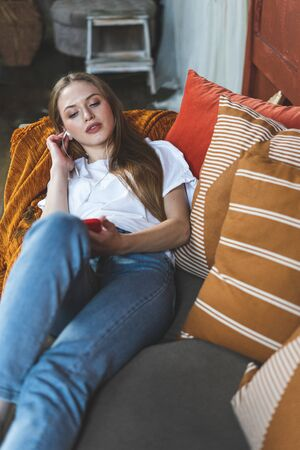 Beautiful young adult girl enjoying day, using earphones on modern smartphone, listening music and spending free time at home, lying on couch in living room