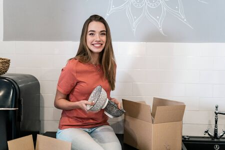 Portrait of happy young adult woman moving in new house with cardboard boxes, sitting on kitchen, packing tableware, holding bowls in hands and looking at camera