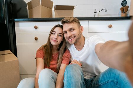 Cheerful young adult husband and wife with cardboard boxes moving in new home, sitting together on kitchen, making selfie photo