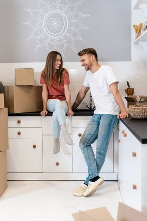 Happy and smiling young family moving in new house with cardboard boxes, standing together on kitchen, talking to each other and making cheerful faces