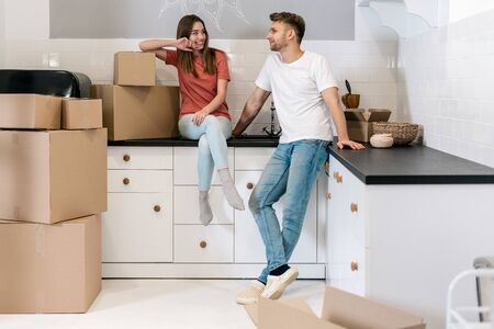 Cheerful young couple with cardboard boxes moving in new house, standing together on kitchen and making happy faces, talking to each other 写真素材