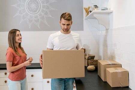 Lovely newlyweds with cardboard boxes moving in new apartment, standing together on kitchen while man looking at package in hands making thoughtful face 写真素材