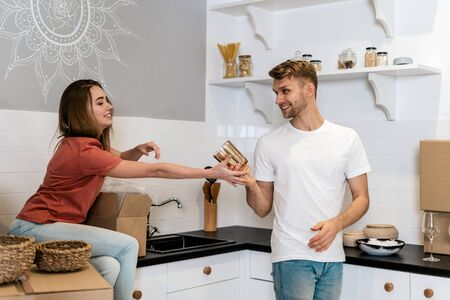 Happy young adult boyfriend and girlfriend moving in new house with cardboard boxes, standing together on kitchen, packing tableware and making smiling faces