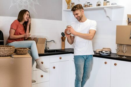 Happy young couple moving in new apartment with cardboard boxes, standing together on kitchen, unpacking carton package, laughing and holding tableware in hands 写真素材