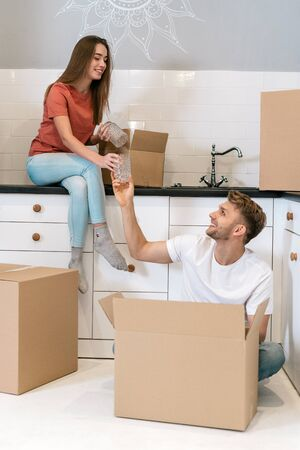 Happy newlyweds with cardboard boxes moving in new home, sitting together on kitchen, unpacking carton package, looking at each other and smiling wide