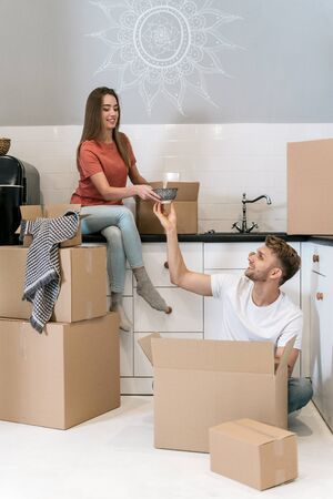 Smiling young adult husband and wife with cardboard boxes moving in new apartment, sitting together on kitchen, packing tableware and making happy faces