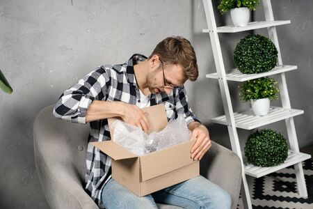 Young adult man holding received carton box in hands, unpacking package, looking inside, checking order and sitting at home with modern interior room