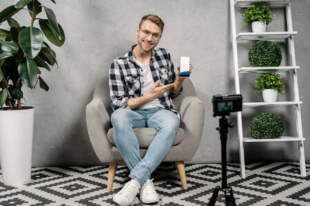 Successful young adult blogger holding smartphone in hands, showing at object, making advertising, creating internet content, recording media and online video on broadcast equipment