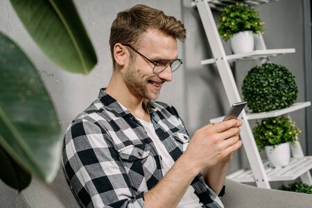 Happy, cheerful young adult guy using modern smartphone, searching new app online, sitting in armchair at home with green plants and grey wall on background