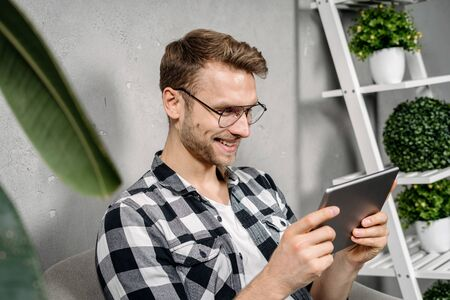 Side view portrait of happy young adult man using modern tablet computer, making smiling face, sitting at home and enjoying weekend day 写真素材
