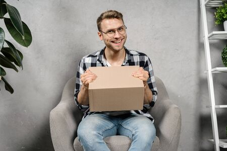 Happy young adult man holding carton box in hands, sitting in comfort armchair, looking at camera with smiling face