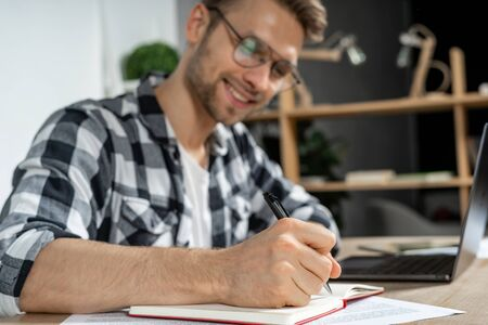 Selective focus on successful young adult businessman writing plans in organizer, sitting in workspace behind table and making beaming smile