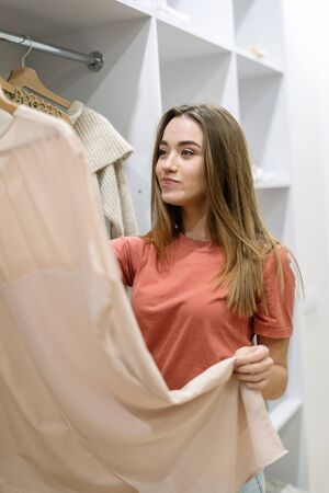 Unsure and minded young adult girl standing near wardrobe, choosing trendy clothes, having difficult choice not knowing what to put on, making thoughtful face