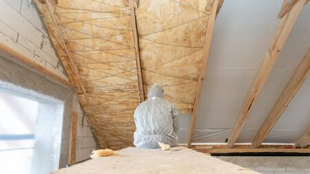 Back view of one worker man in overalls fasten warmth layer material on ceiling and wall of mansard room, working with rockwool insulation, standing inside new house under construction Banque d'images