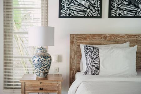 Element of decor at white interior in comfortable bedroom with lamp at wooden, old nightstand near bed inside of lovely house Standard-Bild