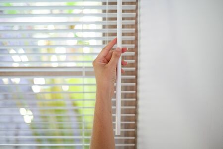 Cropped view of woman closed modern white blinds on windows, making lighting range control in room with copy space on wall Imagens