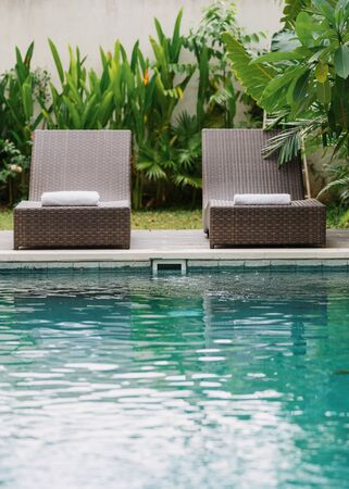 Vertical photo of swimming pool with clear water and white towels on comfort lounge chair standing at poolside against leafy background with green tropical plants