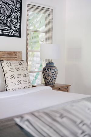 Vertical photo of bright white interior in authentic bedroom with copy space on wall and lamp on bedside table inside of bright flat