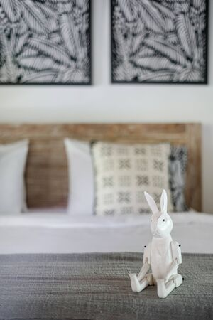 Vertical photo of white interior in cozy bedroom with selective focus at rabbit toy on bed in childrens room inside of elegant apartment