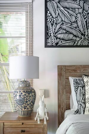 Vertical photo of element white stylish interior in comfortable bedroom at morning. Lamp at nightstand standing near wooden bed inside beautiful house