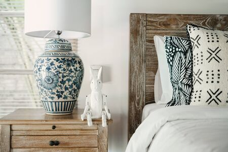 Close up of element white interior in cozy bedroom with comfort bed, lamp and rabbit toy on nightstand inside of lovely house Imagens