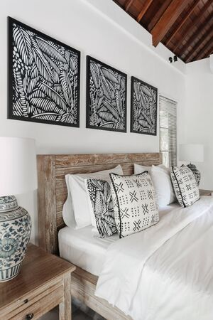 Vertical photo of white stylish interior in comfortable bedroom with lamp on night table near cozy bed inside of bright hotel room Imagens