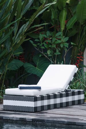 Vertical photo of swimming pool with towel on deck chair standing at poolside against green natural background with exotic foliage Banco de Imagens