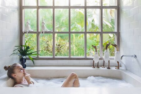 Spa procedure concept. Dreamy and happy young adult woman taking bath, smiling wide, lying in soap foam water, spending free time in bathroom at home 版權商用圖片