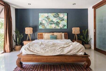 Classic interior bedroom at cozy house with ethnic decor, lamps on wooden nightstand tables, comfortable bed, woven ornament carpet on floor, painting at wall and exotical cactus plant in basket Banque d'images