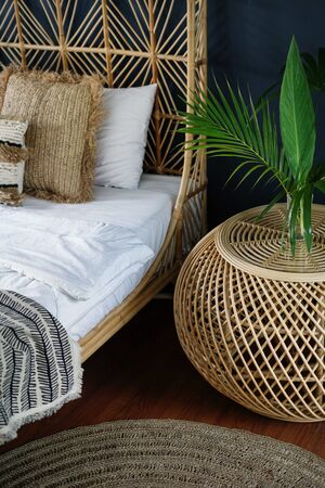 Vertical photo of room with ethnic decor, wicker nightstand table, comfortable bed, carpet or rug and natural green plant composition. Element of classic interior bedroom at cozy house