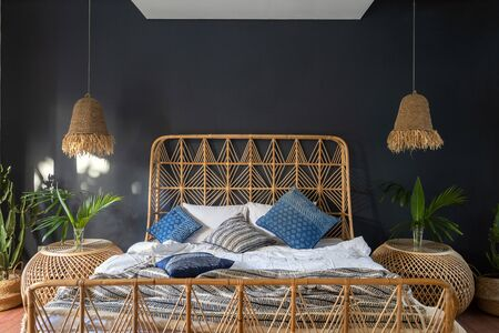Boho chic style at cozy house with ethnic decor. Elegant bedroom interior with lamps over bedside tables, comfortable bed, green cactus plant in basket against blue wall with copy space