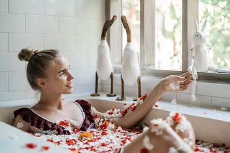 Happy and smiling young adult girl relaxing in bath with tropical flowers and decor toys near windows, spending morning in bathroom