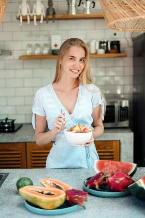 Healthy and seasonal food concept. Vertical photo of happy young adult woman standing on kitchen, eating fruit salad on breakfast, making wide smile