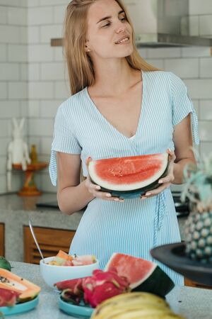 Fresh, diet and healthy food concept. Vertical photo of young adult woman holding watermelon fruit slice in hands, standing on kitchen and smiling nice